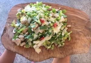 Chicken Cesar Salad on a wooden board.