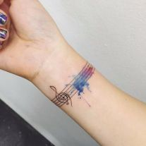 A tattoo showing the G-Clef on a staff but instead of notes and symbols, we ca see a watercolor combination of blue and purple. http://www.piercingmodels.com/music-tattoos/