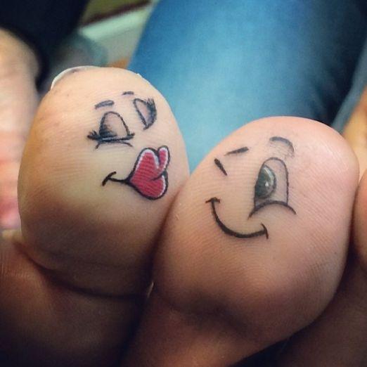 Kissing face tattoo under women toe