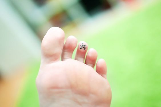 Meow tattoo under toe of foot