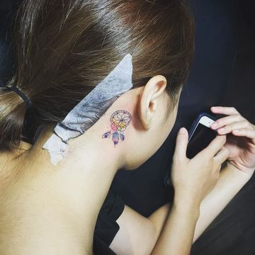 Watercolor dream catcher behind the ear tattoo