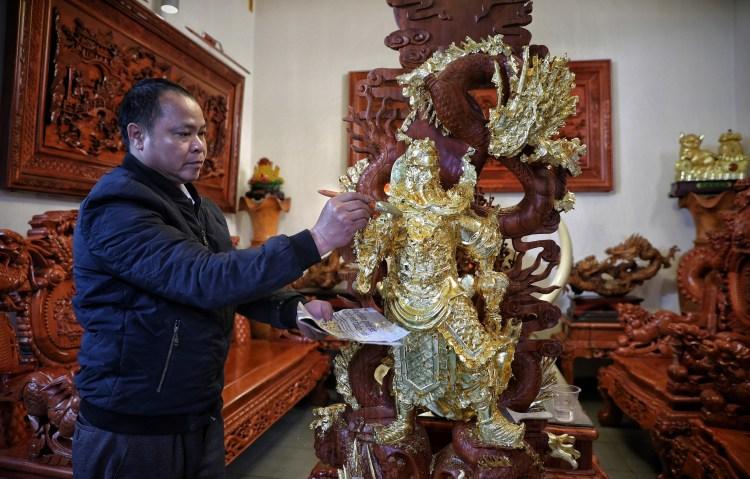 Nghệ nhân Nguyễn Anh Chung thếp vàng lên tượng cho khách hàng. (Ảnh: Danh Lam/TTXVN)