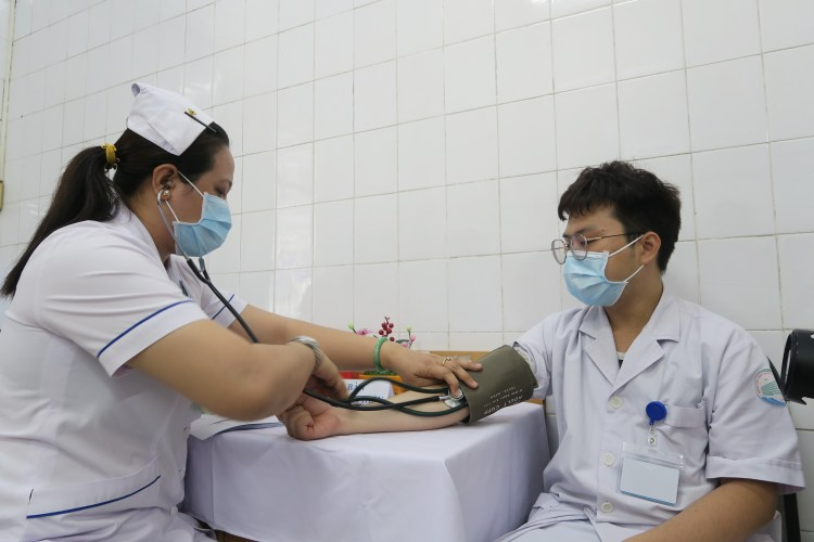 A medical worker receives check-up before getting vaccinated against COVID-19 (Photo: VNA)
