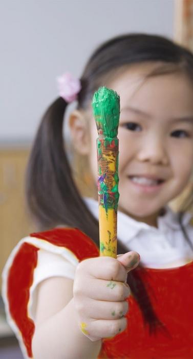 Asian preschool girl with paintbrush