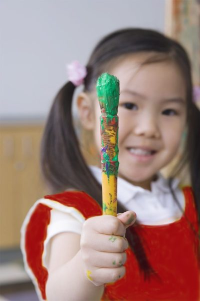 Asian preschool girl with paintbrush