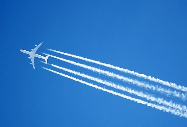 A Boeing 737 sprays chemtrails high above the ground