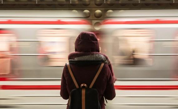 Une personne attends le métro. Nous la voyons de dos. Un train passe rapidement devant elle.