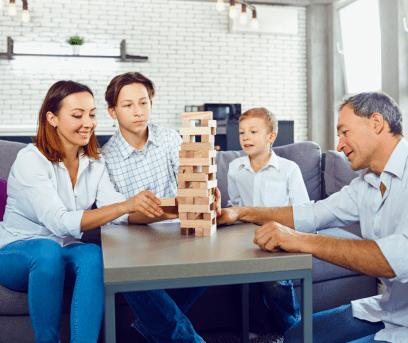 Family sitting around a table playing Jenga