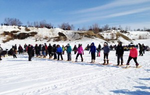 The crowd on the Koyukuk River and along the bank watch as the contestants line up for the Woman's Snowshoe Race. Photo by Dolly Simon-Dayton