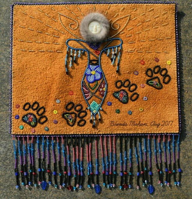 "Athabascan Artist Brenda Mahan made this wall hanging, entitled Alaskan Angel. It is made of moose hide and is 10.5""x12"". Brenda says, ""Alaskan Angels flies high above the Northern Lights (which is the fringe) so that she can have the best view, constantly watching and guarding over everything. Her dog is her constant companion, watching over Alaskan Angel; pure love and always together. Just like her dog, Alaskan Angel will be loyal to you, watch over you and love you unconditionally. Believe in Angels."" Brenda donated it to the Friends of Pets Quilt Auction, which will take place on October 7, 2017, 11 am-2 pm at the University Center Mall in Anchorage, Alaska. Photo courtesy of Brenda Mahan"