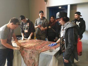 Youth work on cleaning a moose hide at the 2017 First Alaskans Institute Elders & Youth Conference. Melissa Shaginoff hosted this workshop. Photo by Angela Gonzalez