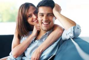 Portrait of a beautiful young couple sitting together on couch at home - Indoor