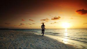 朝日をバックに走る女性