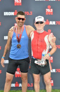 Photo of FitOldDog and Greg with finisher medals for the 2014 Eagleman Half Ironman race.