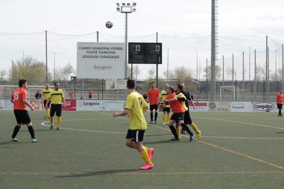 Julio trata de saltar a tocar un balón en el centro del campo ante la carga de un rival.