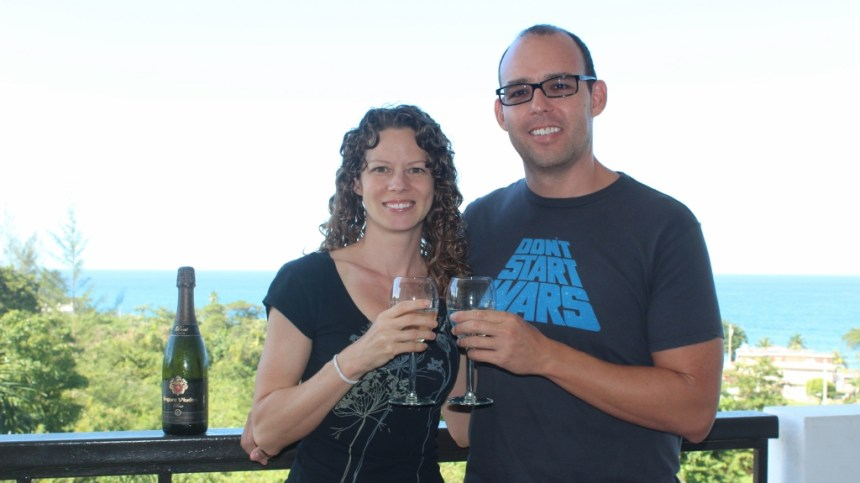 David and Holly holding champange glasses on their balcony