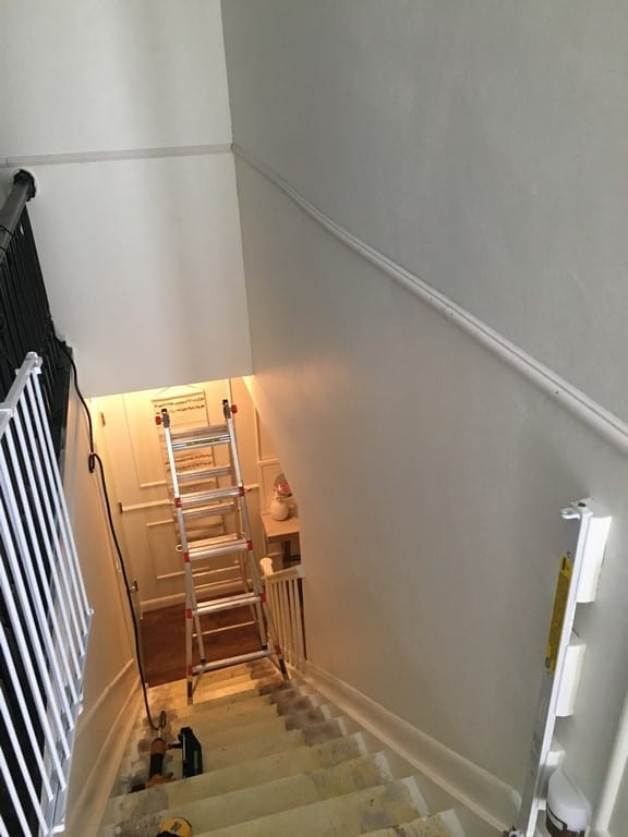 DIY picture frame molding on stairs. How to install modling squares and triangles in a stairway. Tips for installing trim wainscoting in a staircase even with tricky angles