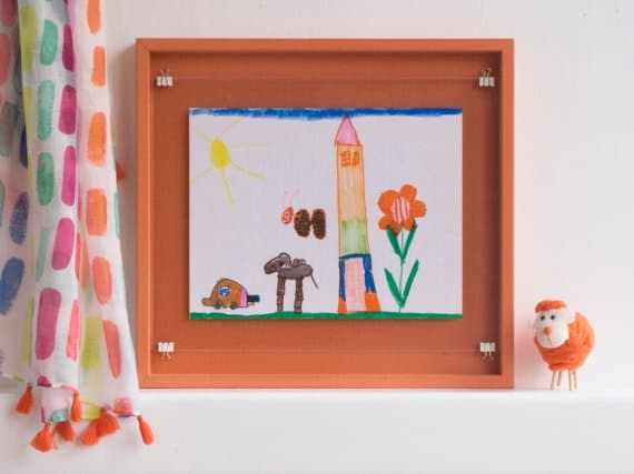 15 ways to display kid art. Are you looking for awesome and fun ways to show off your children's pictures? I'm sharing frames, bulletin boards, twine and products that will showcase kid art. Weather in a hallway, playroom, or bedroom your little artist will love having their art up!