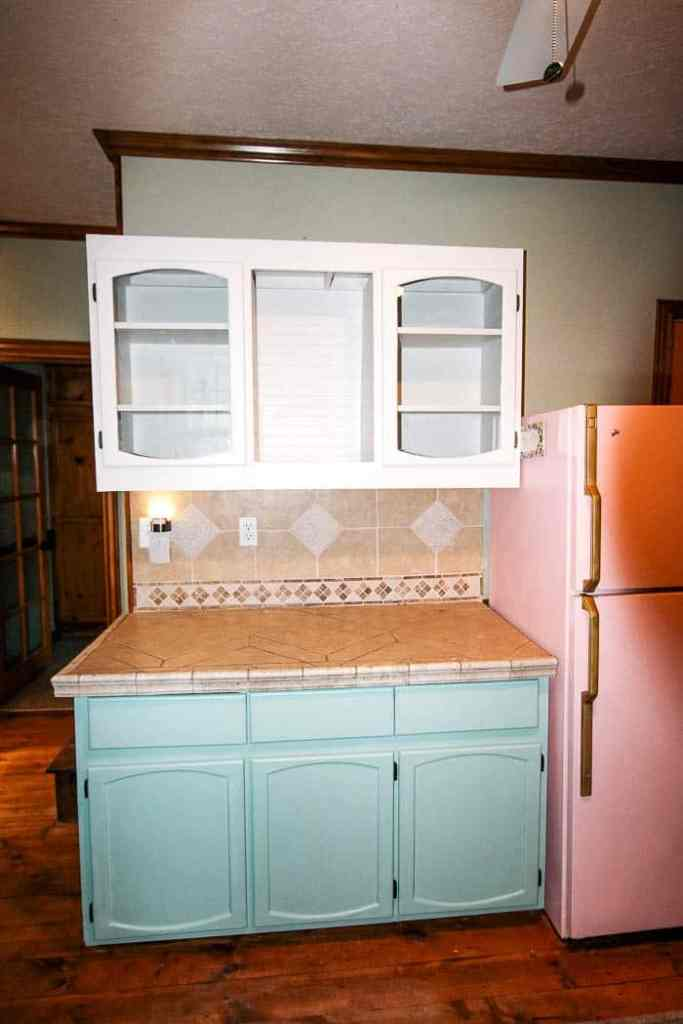 how to paint kitchen cabinets- a step by step guide with chalk paint. This DIY tutorial shows you how to paint without sanding and still have it look like a pro did it! I did white uppers with mint lowers for a two town effect. Includes before and after photos and easy to follow instructions