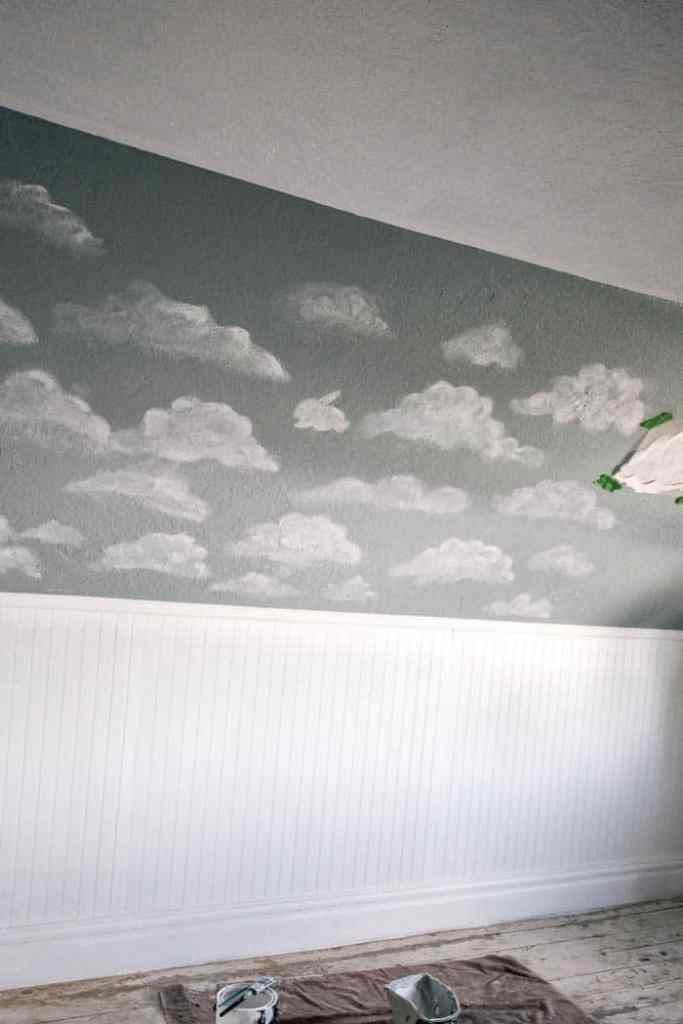 how to paint a cloud mural DIY. This would be beautiful in a nursery or any kids bedroom. Click through for a step by step tutorial with products so you can creat this wall art. I also share ideas and inspiration for adding in cloud animals that your child will love!