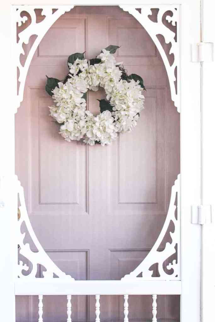 front porch makeover ideas. I redid my porch adding trim to the columns and decor to create Victorian curb appeal. Planters on either side of the pink door and fun decorations add to the overall look. Click through for ideas for how to redo your porch!