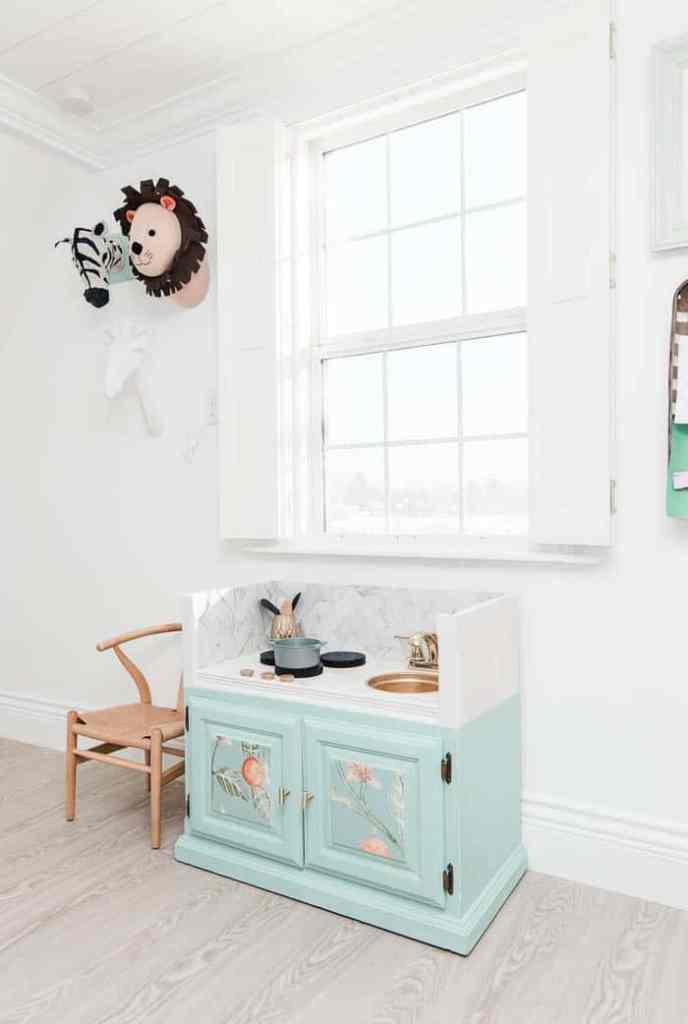 DIY play kitchen. How to make a kids play kitchen from a wooden entertainment center. A retro makeover with the best ideas for how to redo one for a toddler on a budget with interior food storage. Mine is for my son's new playroom so this is perfect for boys.