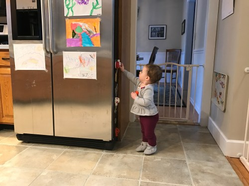 Toddler playing with magnets on refrigerator