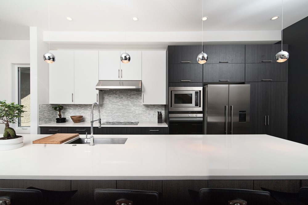 contemporary kitchen with floating lights, quartz counter tops and grey cupboards