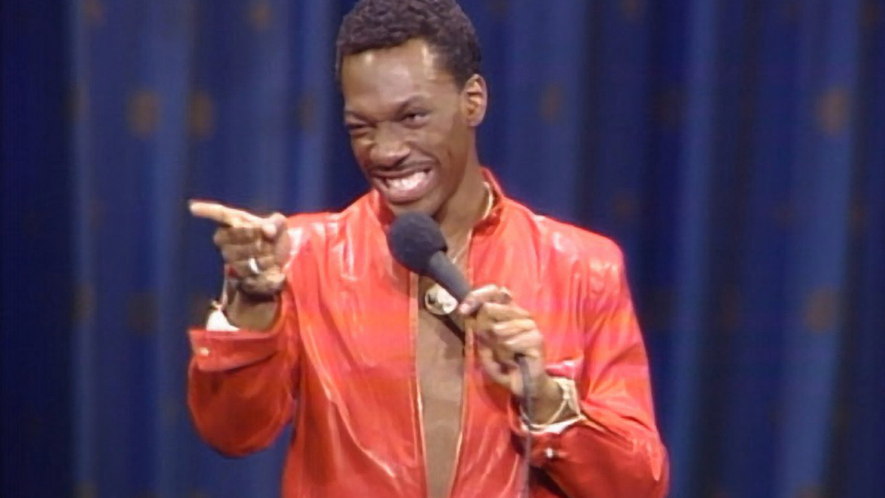 Eddie Murphy on stage wearing a red shirt.