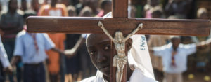 A girl carrying a cross arrives to celebrate mass at Saint Charles Lwanga church in Bangui,  car.  AFP PHOTO / FRED DUFOUR        (Photo credit should read FRED DUFOUR/AFP/Getty Images)