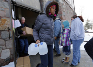 Genetha Campbell carries free water being distributed at the Lincoln Park United Methodist Church in Flint. (Paul Sancya / AP)