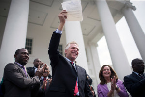 Gov. Terry McAuliffe hold up the signed executive order restoring the voting rights of former felons. Photo by Chet Strange/The New York Times