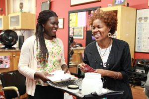 UCLA Ph.D. student Teni Adewumi (left) talks to a hair stylist about the potential risk of some hair products. Adewumi is hoping to persuade the City of Inglewood to pilot a program promoting healthy hair salons.