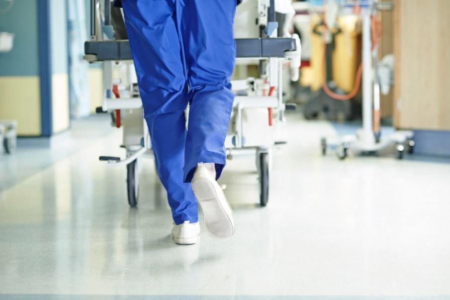 Legs of medic running with gurney along hospital corridorLegs of medic running with gurney along hospital corridor