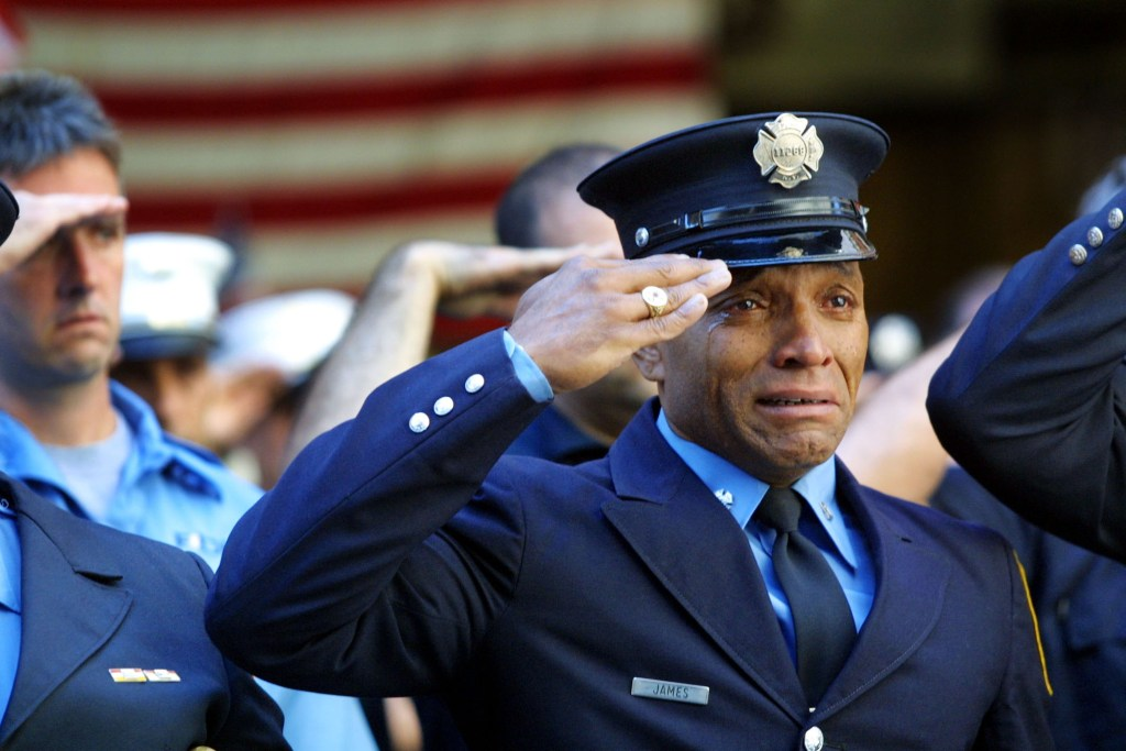 394471 13: Firefighter Tony James cries while attending the funeral service for New York Fire Department Chaplain Rev. Mychal Judge, in front of the St. Francis of Assisi Church September 15, 2001 in New York City. Judge died while giving the last rites to a fireman in the collapse of the World Trade Center. The World Trade Center was destroyed after both the landmark towers were struck by two hijacked planes in an alleged terrorist attack on September 11. (Photo by Joe Raedle/Getty Images)