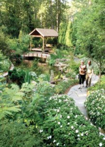 Doug and Jean McGarrity relax beside the third and final water garden they built—this one in place of a former dog run. A pavilion lends the perfect spot for surveying the lush landscape.