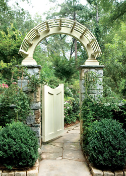 An arched gate at the head of the driveway welcomes visitors to the garden. Japanese maples are pruned to grow like vines on each of the stone pillars.