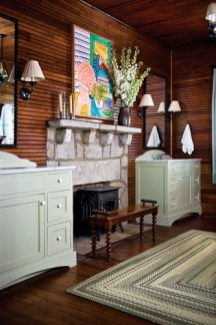 """Glass-paned French doors—relocated from the dining area—now divide the master bedroom from the master bath; because the latter was originally a sitting room, it still has a fireplace as its focal point. """"The whole flow is great,"""" says Loughlin, """"It's like being at camp!"""""""