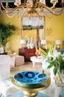 The intense hues of a blue charger, an Oscar de la Renta red-lacquered credenza and a hand-blown glass objet d'art are even more vibrant against maison atlanta's yellow walls.