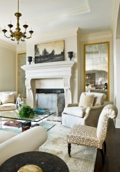 """Flanking the fireplace, wall-hung mirrors reflect not only the beauty of the living room but also the symmetry of the mantel arrangement, which simply consists of two urns and one impressive work of art. """"From the outset, the Finklemans knew that they wanted an uncomplicated look,"""" says designer Carole Weaks, """"and they stayed true to that notion throughout."""""""