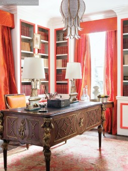 Marcia Sherrill and Summer Loftin created a glamorous study by lacquering the walls in brilliant white and painting the trim blood orange, then echoing the bright color in fabrics from Jim Thompson and a rug from Moattar, Ltd. More than 600 design books from Antonio Raimo Gallery line the room's shelves while a tulip-style chandelier from J Nelson rounds out the designers' glamorous leitmotif.