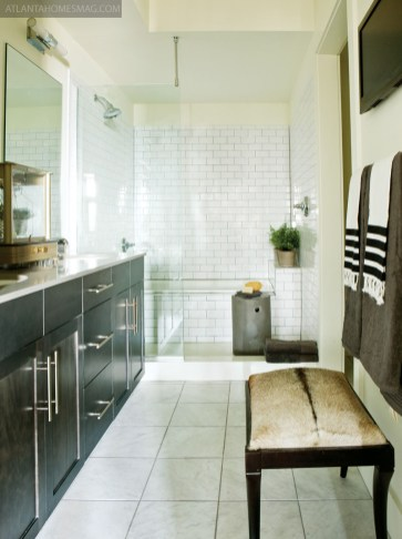In Atlanta, the guest bathroom packs maximum impact thanks to inky black walls, submarine-light sconces and artwork by Todd Murphy, available through Astolfi Art. In the same unit, the master bathroom is at once sleek and cozy, an inviting hide bench helping to enhance this effect.