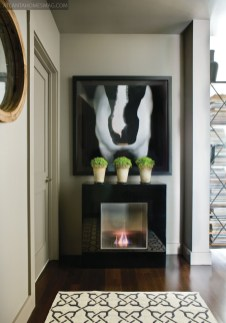 """Stanton warmed up a bare entry wall in his Westside condominium by installing a free-standing fireplace, sourced from Direct Furniture in Atlanta. The equine photography is by artist Ray Hartl, represented at Stanton""""s shop."""