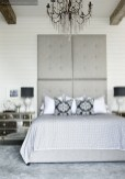 To balance out the hard lines of the planked walls in the master bedroom, the designers added softer, feminine touches: An upholstered headboard, mirrored side table and crystal chandelier give the room an air of laid-back luxury.