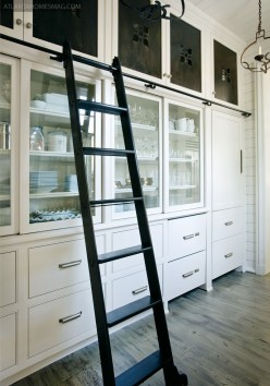 The spacious pantry provides extra storage, allowing the all-white kitchen to remain airy and elegant.