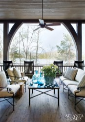 Vintage finds like an antique iron gate-turned-coffee table, as well as the requisite lake house rocking chairs, bring character to the exterior porch, maximizing the family's living space.