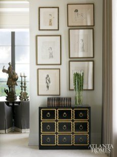 A sextet of framed figures by artist Todd Murphy hangs above a Dorothy Draper chest from the 1940s, creating a quietly sophisticated corner.