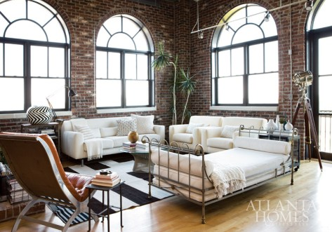 """For Hanson, part of the appeal of this space was its natural light. """"The four grand Palladian-style windows, the patio door and skylights brighten everything,"""" she says. A white-upholstered sofa and pair of matching chairs team with a Maison Jansen campaign daybed to firmly establish the designer's preferred neutral scheme. Sofa and chairs, B&B Italia from Domus. Vintage kilim rug, Sullivan Fine Rugs."""