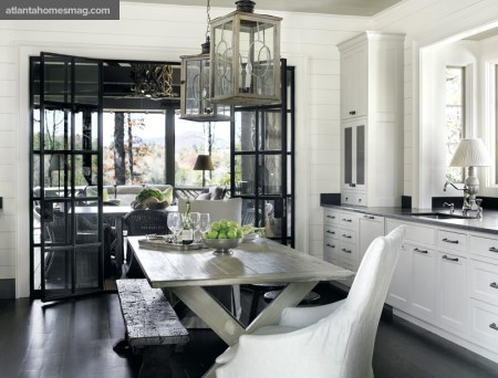 A farm table, eclectic seating and vanishing steel-and-glass doors make the kitchen feel open and fresh, echoing the constant play between textures throughout the house.