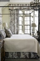 The natural view spills into the master bedroom, where an iron canopy bed strikes a modern touch alongside serene cream, blue-green and brown tones.